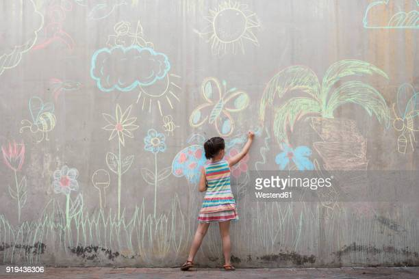 Girl drawing colourful pictures with chalk on a concrete wall