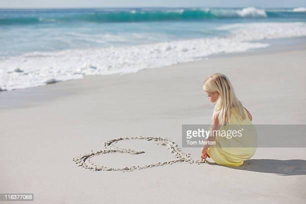 Dessin d'un coeur dans le sable sur la plage