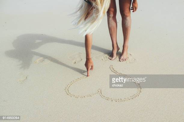 Girl drawing heart shape into the sand