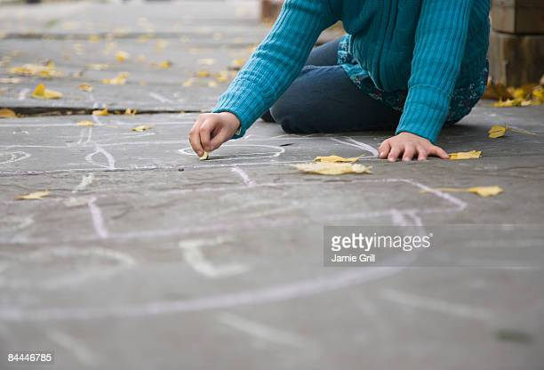 Girl Drawing Hopscotch Court on City Street