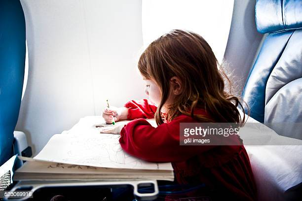 Girl (4-5 years) drawing in airplane