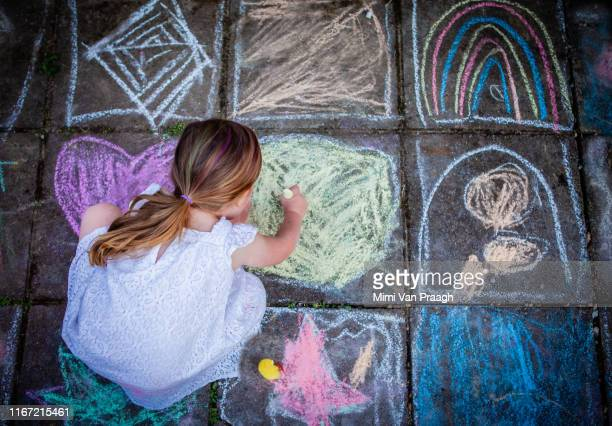 girl drawing in chalk on the floor outside in summer - chalk drawing stock pictures, royalty-free photos & images