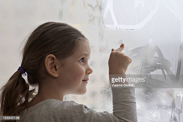 A girl drawing in condensation on glass
