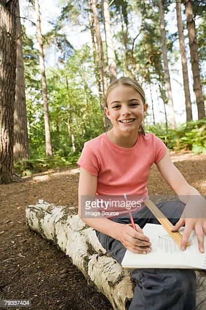 Girl drawing in forest