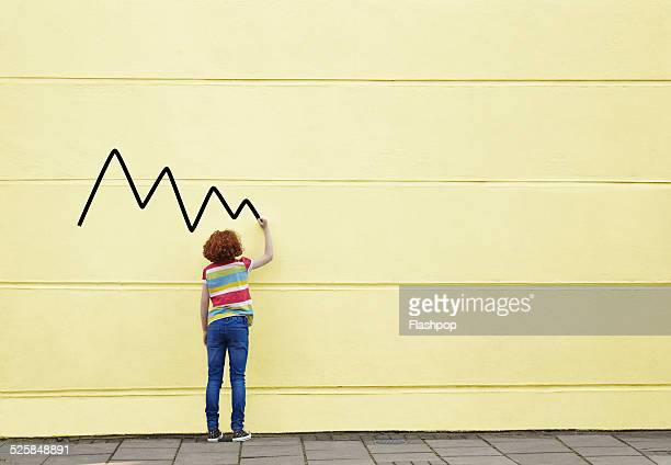 Girl drawing lines on to a wall