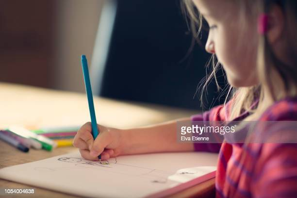 girl (6-7) drawing on a sketch pad on a dining table - art and craft stock photos and pictures