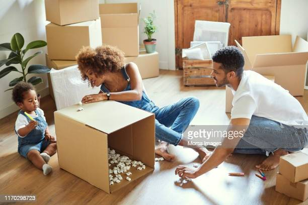 girl drawing on box with parents at new home - unpacking stock pictures, royalty-free photos & images