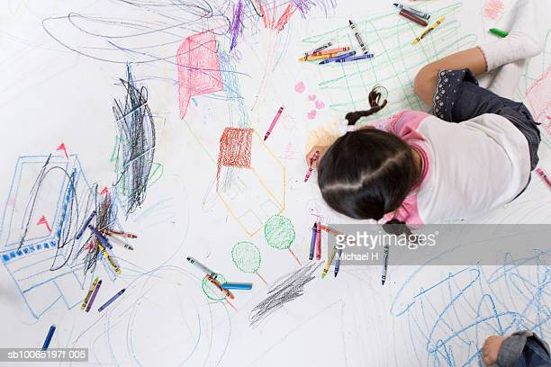 Girl (4-5 years) drawing on floor with crayons, overhead view