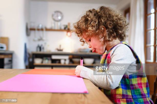 girl drawing on pink paper at table - 4 5 anni foto e immagini stock