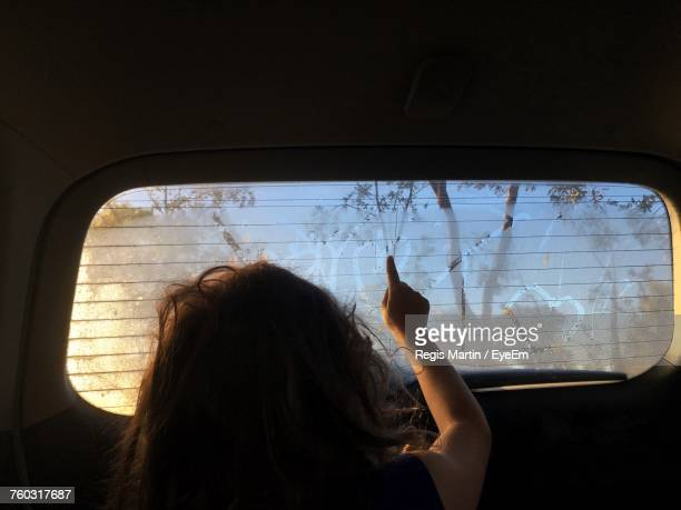 Girl Drawing On Rear Windshield While Sitting In Car