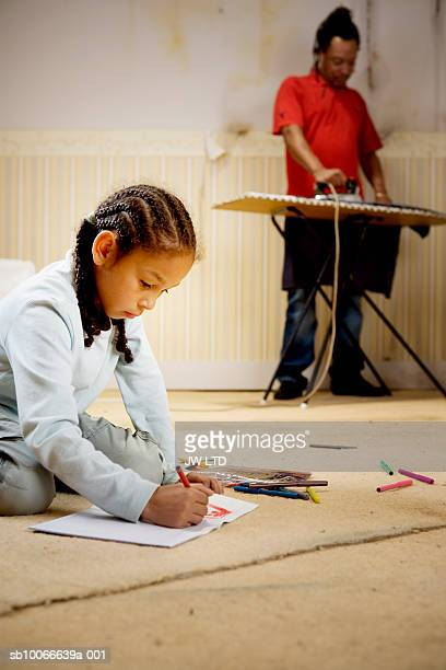 Girl drawing picture, father in background ironing clothes
