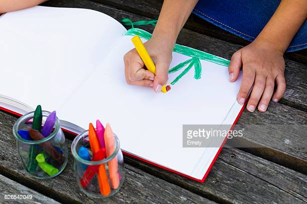 Girl drawing picture in notebook