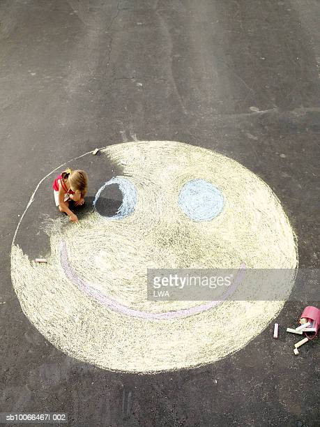Girl (4-5) drawing smiley face on street, elevated view