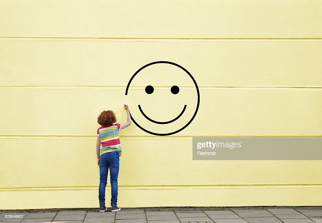 Girl drawing smiley face on to a wall : Photo