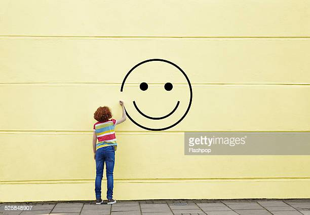 girl drawing smiley face on to a wall - emoción positiva fotografías e imágenes de stock