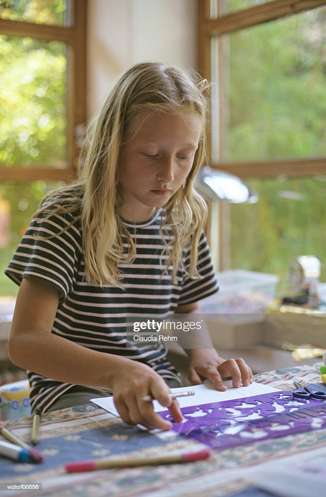 Girl drawing using stencil : Stock Photo