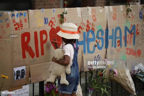 A girl draws on a memorial set against railings in tribute to the victims and the missing from the Grenfell Tower block fire close to the scene in...