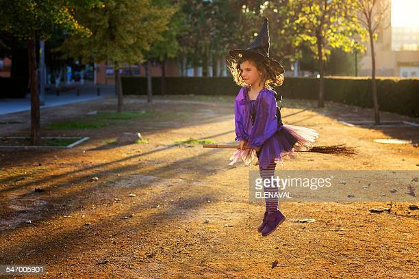 girl dressed as a witch flying on a broomstick - witch flying on broom stock photos and pictures