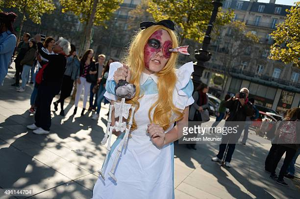 A girl dressed as a zombie of Alice in Wonderland with a dart in her eye poses as she holds a skeletton of a dead puppy during the Paris zombie walk...