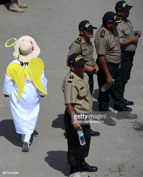 A girl dressed as an angel walks past a group of police officers standing guard during Pope Francis' openair mass at the beach resort town of...