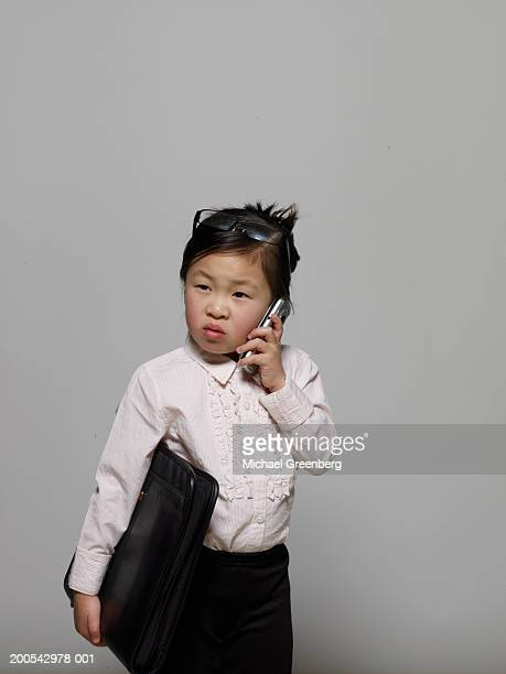 girl (3-5) dressed as businesswoman using mobile phone - adult imitation stock pictures, royalty-free photos & images