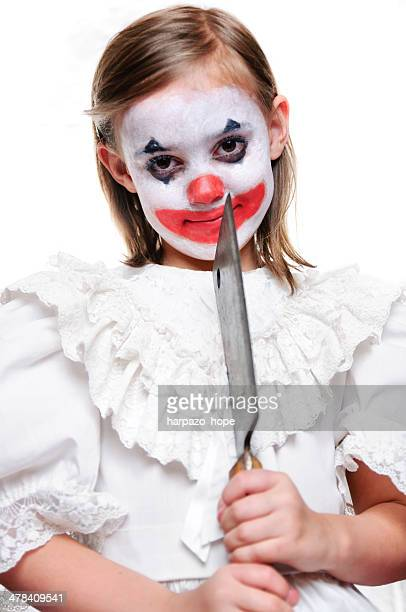 Girl dressed as clown holding butcher knife