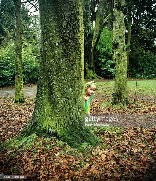 girl (3-5) dressed as fairy, hiding behind tree trunk - karen de silva - fotografias e filmes do acervo