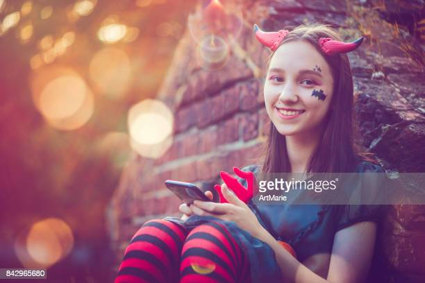 girl dressed as little devil uses smartphone - devil costume stock photos and pictures