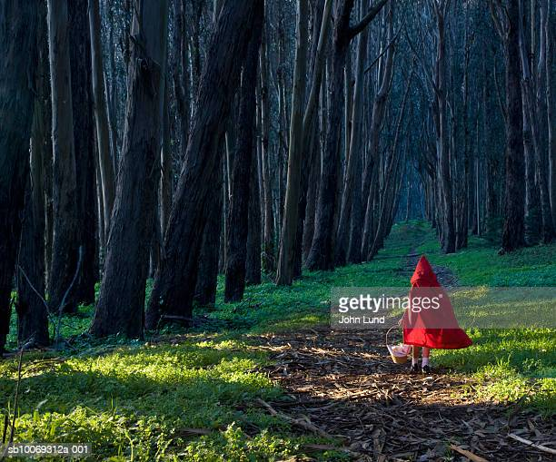 girl (4-5) dressed as little red riding hood in forest, rear view - fairytale stock pictures, royalty-free photos & images