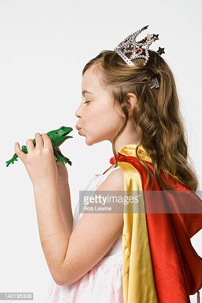 girl (8-9) dressed as princess kissing frog, studio shot - prinses stockfoto's en -beelden
