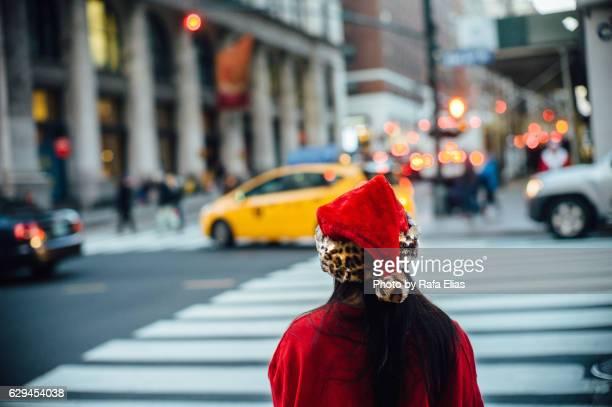 girl dressed as santa claus waiting at zebra crossing - new york weihnachten stock-fotos und bilder
