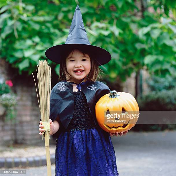 Girl (3-5) dressed as witch, holding pumpkin and broom, portrait