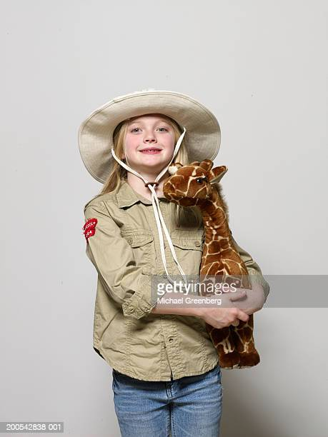 girl (6-8) dressed as zoo keeper, holding giraffe - zoo keeper stock pictures, royalty-free photos & images