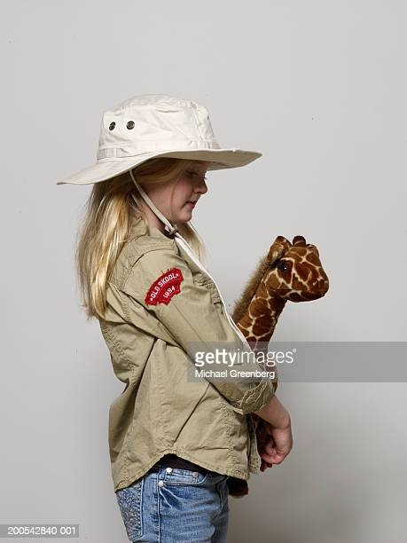 girl (6-8) dressed as zoo keeper, holding giraffe, side view - zoo keeper stock pictures, royalty-free photos & images