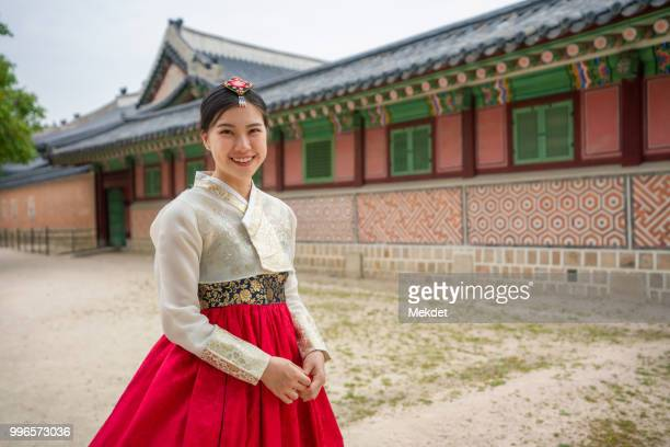girl dressed hanbok (korean traditional dress) in the gyeongbokgung palace of seoul, south korea - gyeongbokgung stock photos and pictures