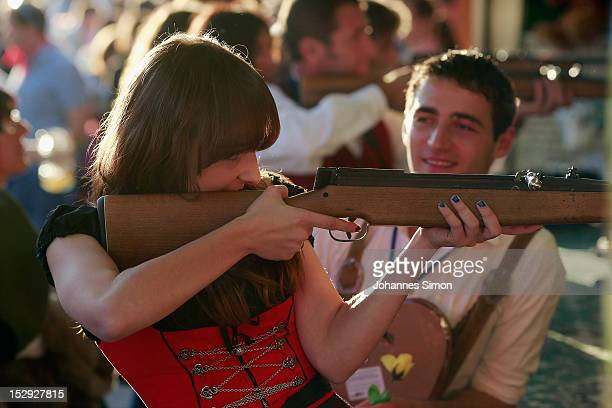A girl dressed in a Bavarian Dirndl fires a rifle at a shooting range during day 7 of Oktoberfest beer festival on September 28 2012 in Munich...
