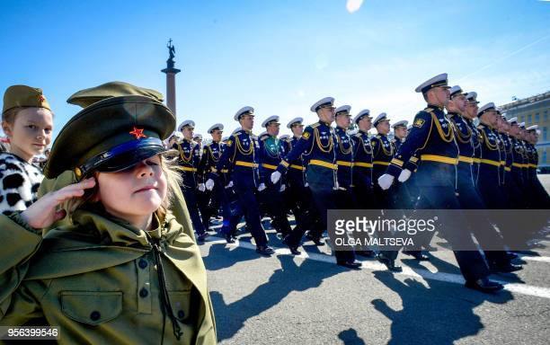TOPSHOT A girl dressed in a Soviet Army styled uniform salutes as Russian military personnel march at Dvortsovaya Square during the Victory Day...