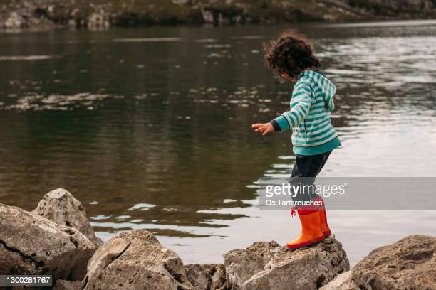 girl dressed in blue striped jacket and orange boots playing on the rocks by the water's edge - ブーツイン ストックフォトと画像
