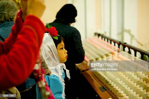Girl dressed in chulapo traditional clothing of the San Isidro kisses the relic of San Isidro during the festivities at Ermita of San Isidro on May...