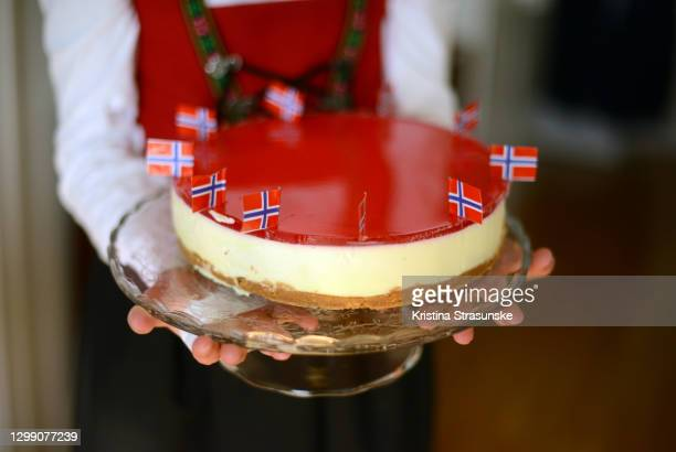 girl dressed in national clothes holding a cheesecake decorated with norwegian flags - norwegian flag stock pictures, royalty-free photos & images