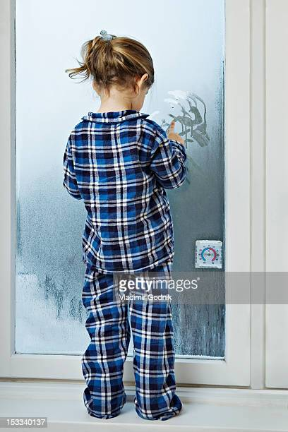 A girl dressed in pajamas and drawing in condensation on glass