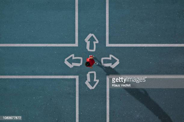 girl dressed in red choosing direction at painted crossroad - richting stockfoto's en -beelden