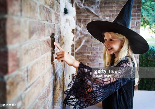Girl dressed in witch costumes ringing door bell