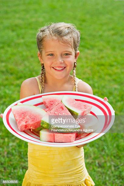 """girl dressed in yellow holding plate of watermelon - """"compassionate eye"""" stock pictures, royalty-free photos & images"""
