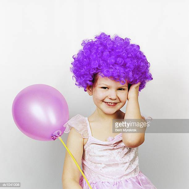 Girl Dressed Up as a Clown Sitting Holding a Purple Balloon