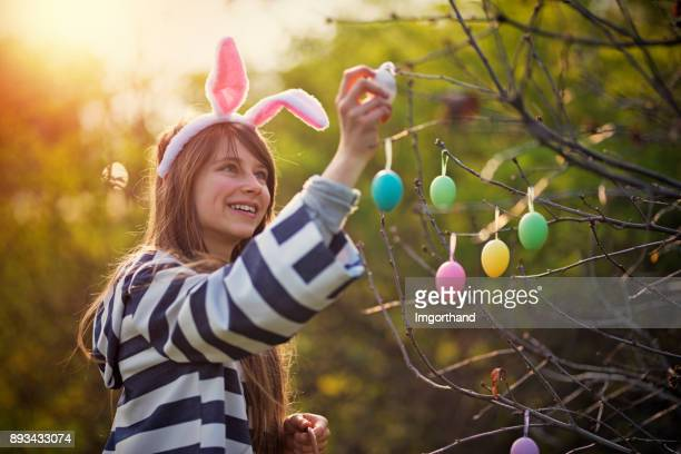 Girl dressed up as easter bunny hanging easter eggs