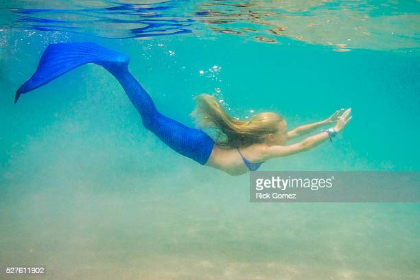 Girl (8-9) dressed up as mermaid swimming underwater