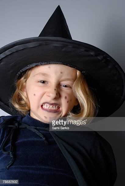 Girl (5-7) dressed up as witch for Halloween, making scary faces