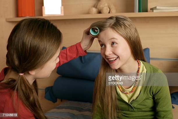 girl dressing friend's hair - krulspelden stockfoto's en -beelden
