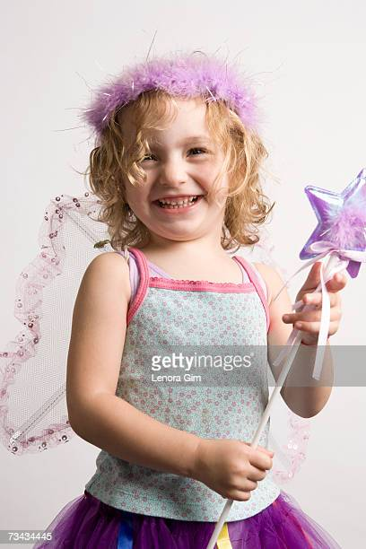 Girl (2-4) dressing up in fairy costume, smiling, portrait